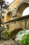 Pont du Gard, in Provence, France, over the Gardon river, is an 160 foot high roman aqueduct built to provide water to the city of Nimes from the river Eure near Uzes, in the first century A.D. poster