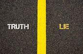 Antonym concept of TRUTH versus LIE written over tarmac road marking yellow paint separating line between words poster