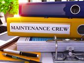 Yellow Ring Binder with Inscription Maintenance Crew on Background of Working Table with Office Supplies and Laptop. Maintenance Crew Business Concept on Blurred Background. 3D Render. poster