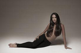 Gorgeous young woman posing in studio wearing black leggings.