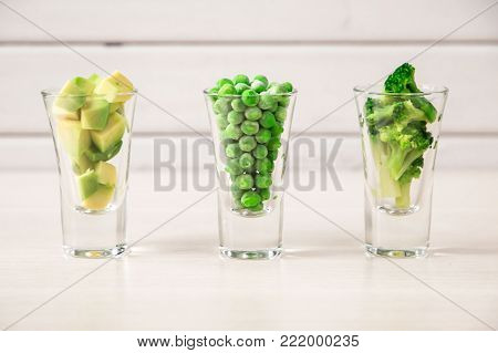 closeup of assortment of green cut vegetables in shot glass on white background.