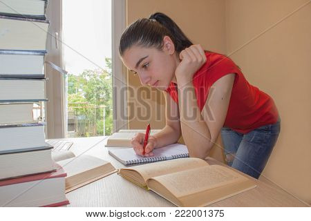 Young Girl write in notebook between books. young attractive student Girl studying lessons