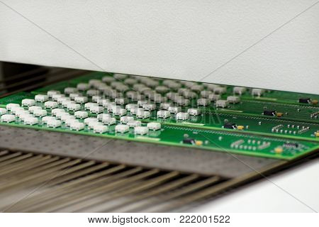 Electronic printed circuit board at the output of air convection reflow oven.  Manufacture of electronic components.