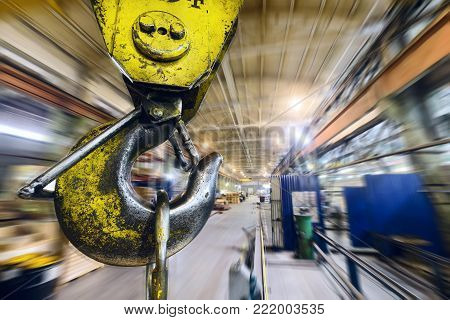 Powerful hook crane close-up. Against the background of the industrial plant. Abstract industrial background, motion blur effect.