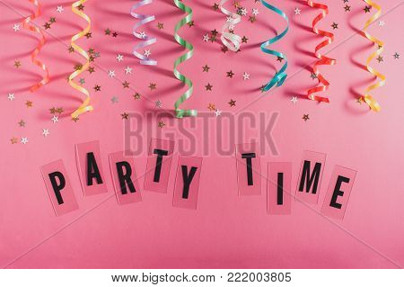 Colorful party streamers, gold little stars and text Party time on pink background. Girly birthday concept. Flat lay.
