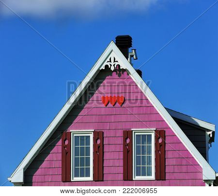 Detail of a beige rooftop with three red wooden hearts shape in Iles de la Madeleine in Canada