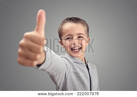 Boy with thumbs up agreeing and giving his approval