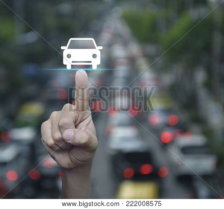 Hand pressing car flat icon over blur of rush hour with cars and road, Business transportation taxi car service concept
