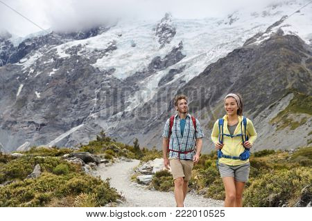 New Zealand backpackers tramping on Mount Cook / Aoraki Hooker valley travel. Backpacking hikers hiking walking on Hooker Valley Track. Snow capped mountains glacier landscape. Couple on summer hike. poster