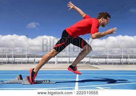 Runner athlete starting running at start of run track on blue running tracks at outdoor athletics and fiel stadium. Sprinter. Sport and fitness man running sprinting.