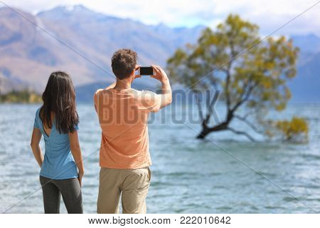 New Zealand tourists taking phone pictures of Wanaka Lone Tree at lake. People looking at view of famous touristic attraction in south island, Otago Region, NZ.