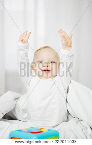 Frisky baby in white crawlers sits on comfortable bed with raised hands and smiles in front of toy in form of cube surrounded with warm blanket.