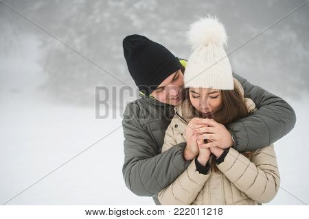 Couple shivering outdoors in winter, rubbing hands.