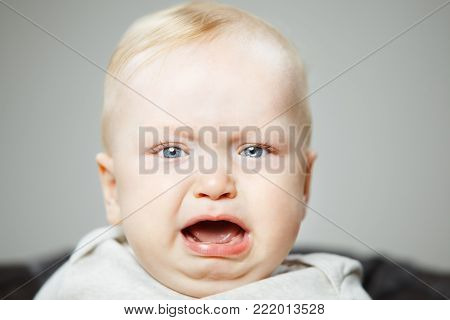 Disappointed charming blond baby boy cries hard with big light eyes, long lashes, arched eyebrows, plump cheeks and wide open mouth portrait photo.