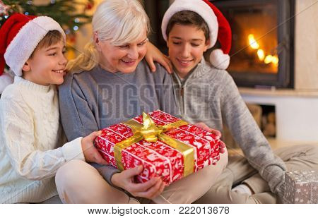 Grandmother With Her Two Grandchildren, Holding A Christmas Gift