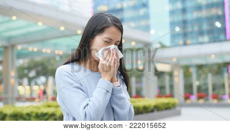 Woman sneeze at outdoor city