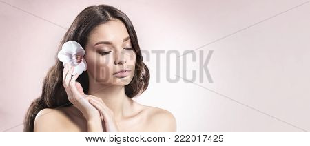 Young and healthy woman with light make-up and Orchid flower in her hair on light pink background. SPA and skin care concept. Copy space.