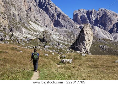 A tourist hiking in Val di Gardena in the Dolomite Alps