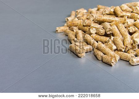 Biofuels. Wood pellets on a silver background.Pellets Biomass - cheap energy.