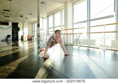 Lawyer with good body doing different pushups, tattooed guy relieve stress after hard working day. Fair-haired boy on training in well-equipped gym with ballet barre and big windows. Concept of individual workout, spacious hall or sportswear