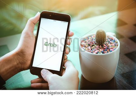 CHIANG MAI,THAILAND - Nov 11 2017 :MAN hand holding Grab app showing on iphone 6s in coffee shop. Grab is smartphone app-based transportation network.