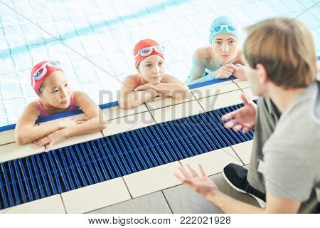 Row of schoolkids listening to their swim trainer instructions while standing in water