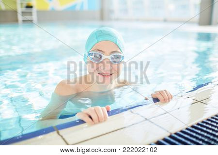 Young swimmer in swim-cap and goggles standing in pure water of swimming-pool