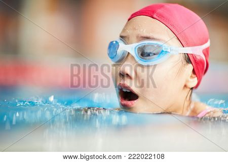 Little swimmer in swim-cap and goggles breathing over water while swimming