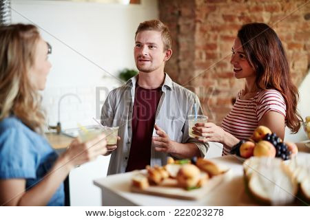 Two girls and guy with drinks having talk in the kitchen at home party