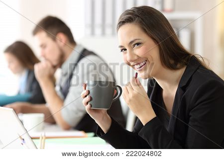 Happy businesswoman taking a pill and looking at camera at office