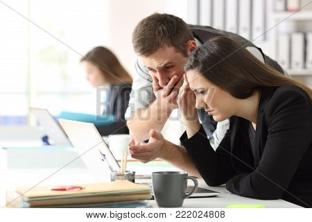 Two worried office workers checking online content in a laptop