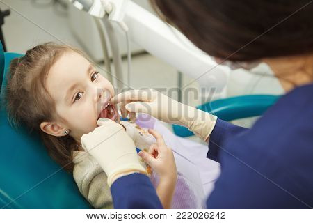Professional dentist in rubber gloves checks mouth of child that lies on comfortable leather chair with wide open mouth and comes through simple examination procedure.