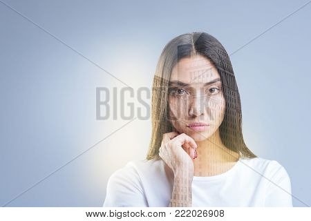 City creation. Serious wistful hopeful woman gazing at the camera while reflecting and holding hand near face