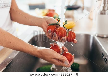 Woman washing tomatoes in kitchen sink close up