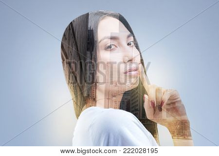 Nice idea.  Beautiful irresistible creative woman looking at the camera while posing on the isolated background and demonstrating finger