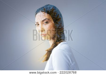 Serious concern. Earnest focused tranquil woman posing on the isolated  background while protecting her point of view and staring  at the camera