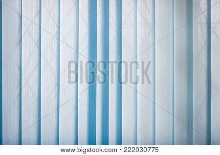 Background of the blue vertical blinds made with stiffened fabric in closed position