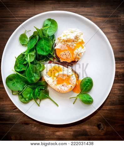 Delicious poached eggs on the big white plate on the wooden table, beautiful tasty food still life, traditional breackfast, healthy organic nutrition