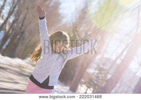 Beautiful smiling schoolgirl with raised up hands enjoying warm sunny weather in wintertime in the park, happy winter holidays, baby in good health embrasing life, wellness concept