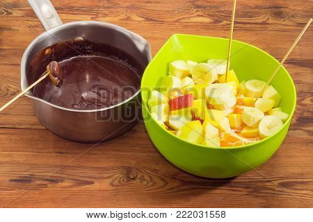 Chocolate fondue - pot with melted chocolate mixture and green plastic container with pieces of different fruits and bamboo wooden skewers on an old rustic wooden table