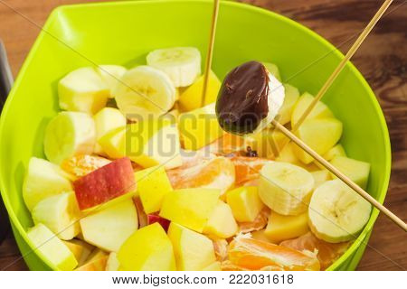 Fragment of chocolate fondue - piece of fruit on a bamboo wooden skewer, dipped in liquid chocolate over container with pieces of different fruits closeup at shallow depth of field on a rustic table