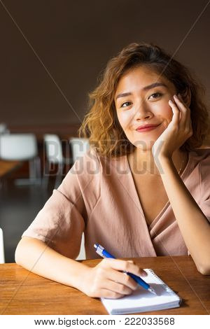 Closeup of smiling young Asian woman at cafe leaning head on hand and writing in notebook. Positive student drafting plan of research paper. Writing and education concept