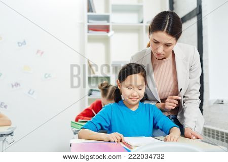 Adorable schoolkid and her teacher thinking of new ideas of picture at drawing lesson