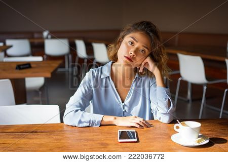 Closeup of serious young Asian woman sitting at table with mobile phone and coffee and leaning head on hand, Businesswoman thinking over challenge at coffee shop. Business and decision making concept