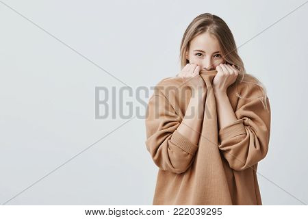 Pretty female with fair straight hair and dark appealing eyes hiding her face in warm loose sweater. Studio shot of good-looking beautiful girl isolated against gray studio background.