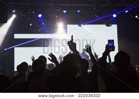disco at a concert with light music spectators with their hands up