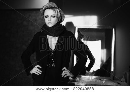 Black and white art monochrome photography. Black and white creative photography. Black and white conceptual image. Beautiful black and white background. Black and white portrait. Lovely girl with tanned skin and white hair in a hat and black jacket.