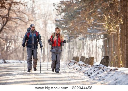 Young couple of mountaineers hiking on winter in nature