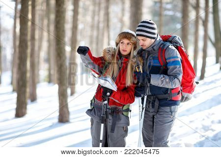 Young hikers looking and showing right way on map
