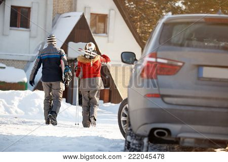 Skiers couple with ski equipment, on winter holiday back view